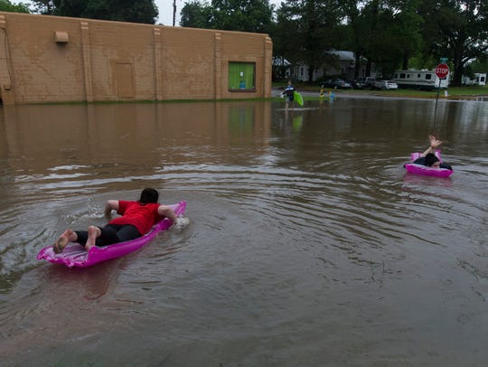 Young women float on air mattresses down a flooded