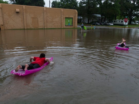 Young women float on air mattresses down a flooded Carencro street as flash floods swept through Acadiana Sunday.