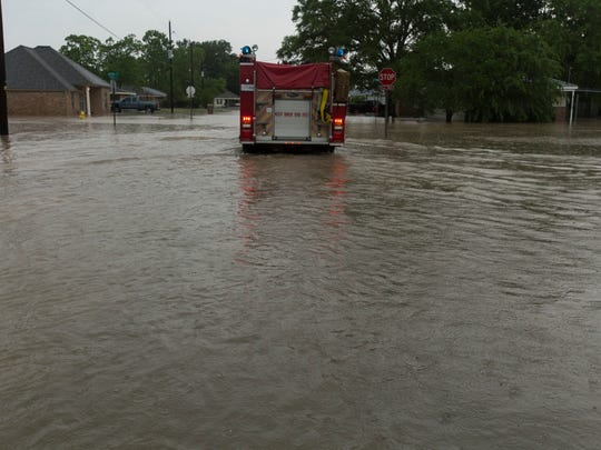 A firetruck makes its way down a flooded Carencro street as flash floods swept through Acadiana.