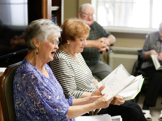 Betty Roy- left, with her sister Mavis Fruge, reads L'Arbre Genereux (The Giving Tree) to nursing home residents in Arnaudville June 23, 2016.
