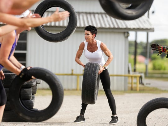 Bodybuilder Jessica Wright-Wiltz helps her boot camp clients throw tires as part of their training at her gym in Lafayette July 7, 2016.