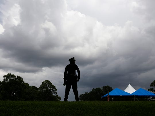 A police officer stands watch Monday before the internment