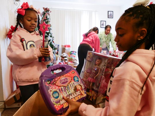 Ke'ani, left, and Shania Page open Christmas gifts