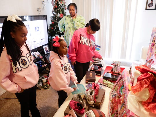 Shania, left, and Ke'ani Page look over Christmas gifts they received after a wishlist to Santa Claus on a balloon was found, in Lafayette Monday, Jan. 9, 2016.