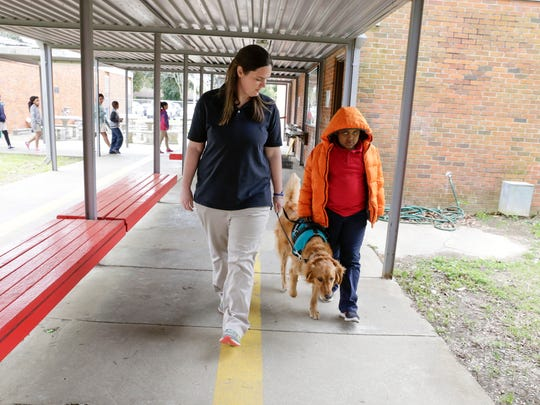 Teacher Sarah Gros and student Christopher Roberts walk with Roux, a therapy dog, at J.W. Faulk Elementary in Lafayette Monday, March 13, 2017.