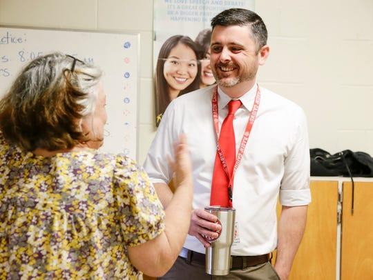Principal Stephen Judice talks to a staff member at