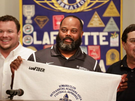 St. Martinville Head Coach Vincent DeRouen holds up