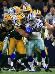 Cowboys running back Ezekiel Elliott (21) is wrapped up by Packers outside linebacker Nick Perry (53) during the second half of an NFL divisional playoff football game on Jan. 15 in Arlington, Texas.