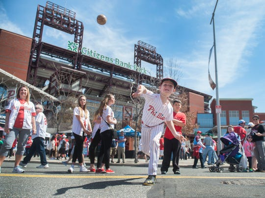 Stephen Devanney, 8 of Pitman, throws a pitch while playing a baseball themed game during the Citizens Bank Way Opening Day Party held before the Phillies home opener at Citizens Bank Park in Philadelphia Monday.