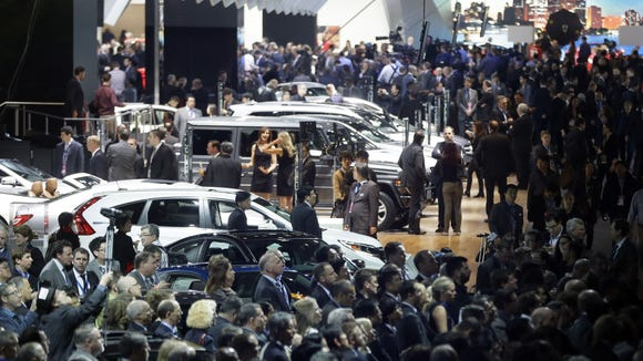 Journalists crowd the floor during the North American International Auto Show, Monday, Jan. 12, 2015 in Detroit. (AP Photo/Carlos Osorio)