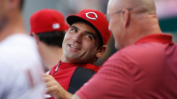 Injured Reds first baseman Joey Votto talks with head athletic trainer Paul Lessard on Aug. 27.