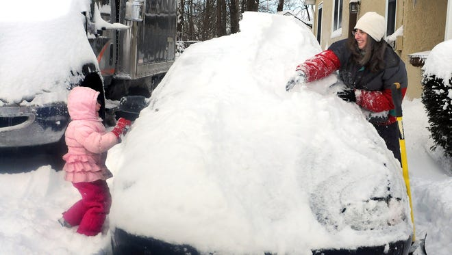 In this file photo, Camille Foerst, 4, left, helps her mom, Alysia, clear snow from their car last winter along South Grand Avenue in Poughkeepsie.