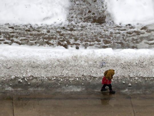 A woman avoids the slushy sidewalk as she walks down East Franklin Street in Appleton on Tuesday.