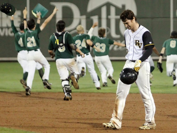 Bishop Verot High School's Gunnar Joslin leaves the field as Trinity Catholic players celebrate beating Verot in the Class 4A state semifinal on Wednesday at jetBlue Park in Fort Myers. Joslin made the game's final out.