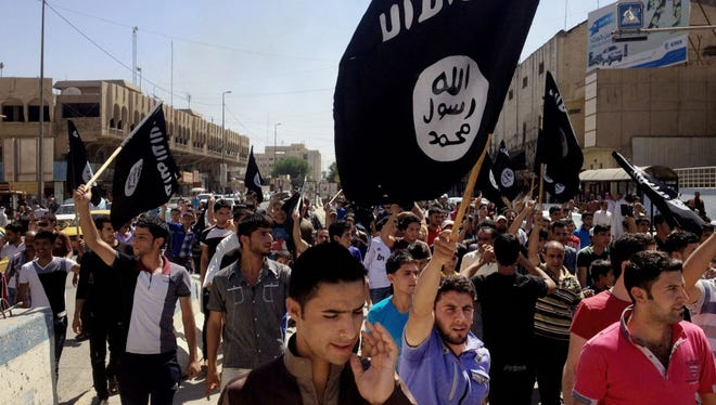 Demonstrators chant pro-Islamic State group slogans as they carry the group's flags in Mosul, Iraq, June 16, 2014.