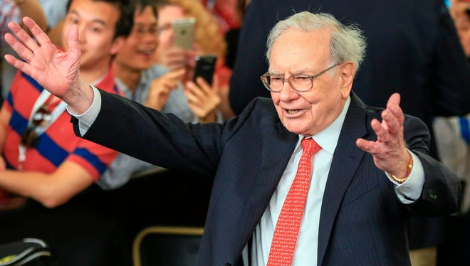 In this May 3, 2015, file photo, Berkshire Hathaway Chairman and CEO Warren Buffett lifts his arms to greet table tennis prodigy Ariel Hsing, unseen, before briefly playing some table tennis outside the Borsheims jewelry store, a Berkshire Hathaway subsidiary, in Omaha, Neb.