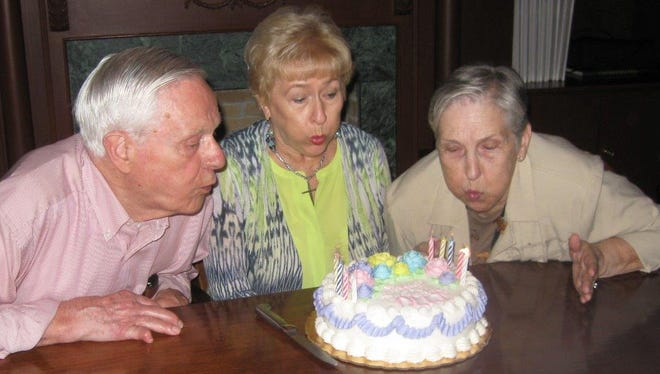 Sue Pace, center, founding director of OLLI, helps charter members Tom and Jeanette Price blow out the candles on the OLLI birthday cake. OLLI is celebrating 25 years.