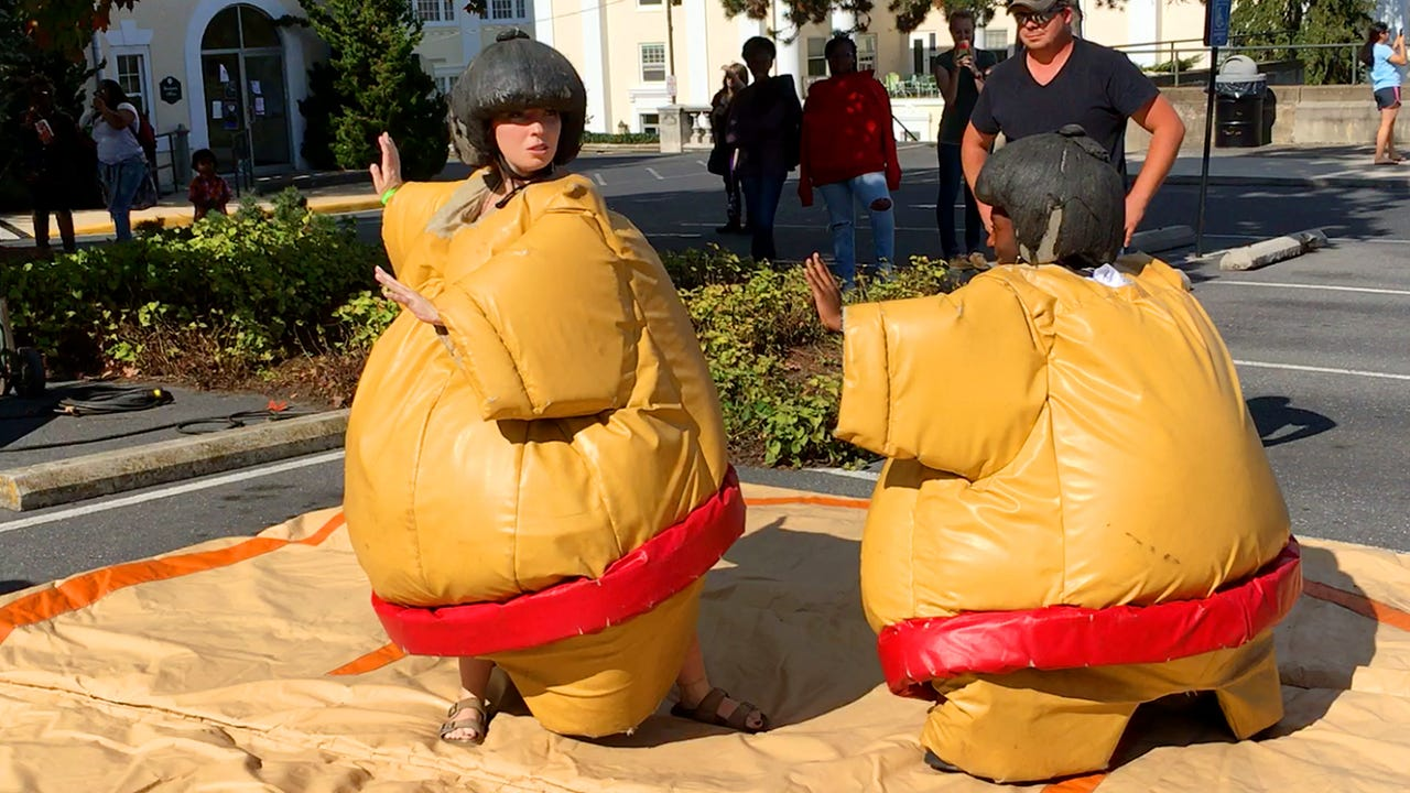 Sophomores Elisa Bakker and Kyle Carter of Mary Baldwin University square off in a wrestling match wearing padded sumo wrestling suits during the school's annual Apple Day carnival on Sept. 4, 2016.