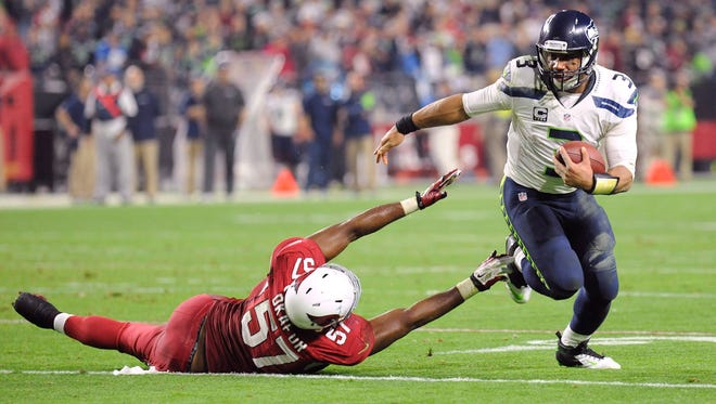 Dec. 21, 2014; Glendale; Seattle Seahawks quarterback Russell Wilson (3) sheds the tackle of Arizona Cardinals outside linebacker Alex Okafor (57) en route to a touchdown run during the second half at University of Phoenix Stadium. The Seahawks won 35-6.