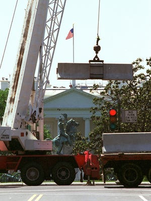 With the White House in the background, construction workers place traffic barricades along Pennsylvania Avenue in Washington in this May 20, 1995 photo.