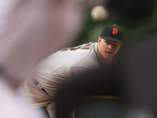 San Francisco Giants starting pitcher Matt Cain, back, delivers a pitch while framed by Colorado Rockies batter Troy Tulowitzki, front left, and home plate umpire Adam Hamari in the first inning of a baseball game in Denver on Wednesday, May 21, 2014. (AP Photo/David Zalubowski)