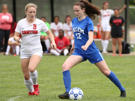 Salem senior forward Katie Coleman (12) dribbles past