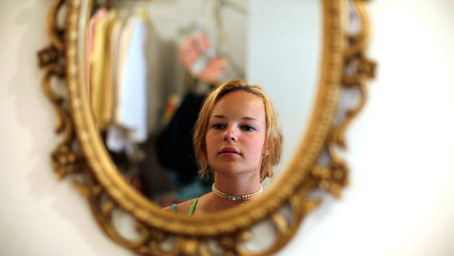 Thursday, June 27, 2012: VINE STREET:  Evelynn Wyatt, 16, of Louisville, admires a pearl choker in the mirror at Mannequin, a resale boutique at 1405 Vine Street. Wyatt was with family members doing some shopping along Vine Street. The shop has been at it's present location for the past year-and-a-half. The shop has many top designer labels and also an entire room dedicated to vintage clothes and accessories. Everything is donated and proceeds go directly to seven different local charities.  My Voice: I was supposed to be working when I was making this photo, but I ended up purchasing two necklaces. I love this place. The color, the vintage clothing and the wonderful mannequins. It's a great treasure on Vine Street.