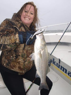 Sam Franklin of Danbury, Connecticut holding the striped bass she caught while fishing with Alex Majewski on LightHouse Sportfishing.