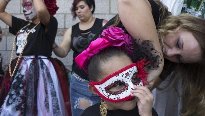 Sara Camarillo (right) gets her daughter, Gianna Camarillo (4), a member of Folklorico Lindo y Querido, ready to perform, October 25, 2014, at the Mesa Arts Center's celebration of Dia de los Muertos.