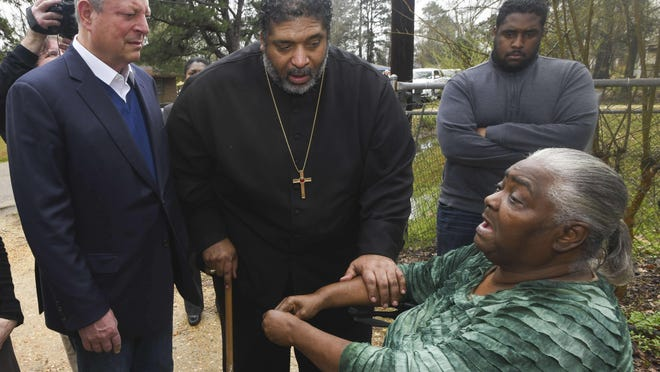 "FILE - In this Feb. 21, 2019, file photo, former Vice President Al Gore, left, founder of the Climate Reality Project, and the Rev. William Barber II, president of the Repairers of the Breach, visit Lowndes County resident Charlie Mae Holcombe to talk about the failing wastewater sanitation system at her home in Hayneville, Ala. An anti-poverty coalition led by Barber is scheduled to hold a virtual march Saturday. The Mass Poor People's Assembly & Moral March on Washington aims to build upon the nation's principles to pursue solutions to poverty â€"" something advocates say is getting especially severe in rural areas."