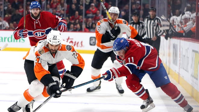 Philadelphia Flyers center Boyd Gordon and Montreal Canadiens right wing Brendan Gallagher battle for the puck during the first period of Monday's game.