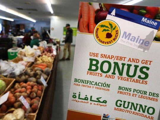 A sign advertises a program that allows food stamp recipients to use their electronic benefit transfer cards to shop at a farmers market in Topsham, Maine. Some cities and states are experimenting with ways to entice food stamp recipients to eat more fruits and vegetables.