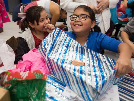 Kanla Galavis unwraps a present during Crockett Elementary's second annual Christmas Tree Angel event on Wednesday, Dec. 13, 2017.