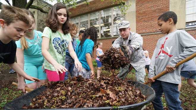 Lt. Col. Jeff Charette of the 179th Airlift Wing Ohio Air National guard pitches in as he helps students from the Spanish Immersion School clean up in the front of the building.