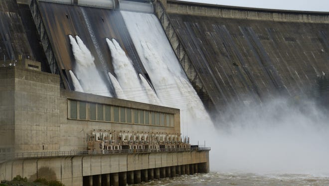 Officials open one of the drum gates atop Shasta Dam on Wednesday afternoon for a test. It was first time in 19 years that water has spilled from the gates.