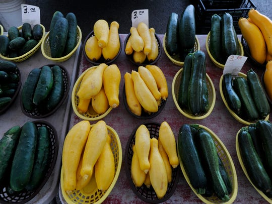 Squash, zucchini and cucumbers rest in baskets for