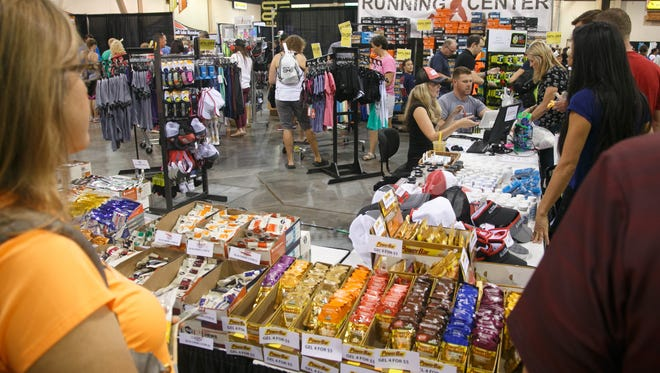 Runners wait in line to make their purchases at the St. George Running Center's booth at the St. George Marathon Altra Health and Fitness Expo at the Dixie Center in St. George, Friday, Oct. 2, 2015.