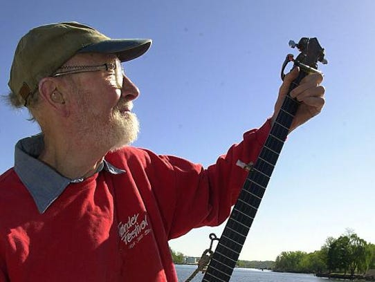 Pete Seeger plays the banjo aboard the Hudson River