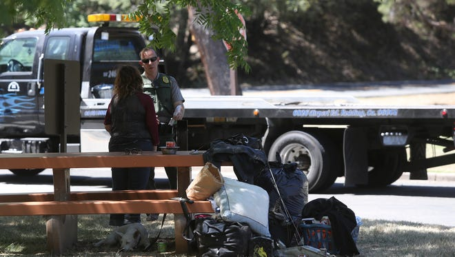 Acting Chief Ranger Dave Keltner talks with a woman Tuesday in the parking lot of the visitors center at Whiskeytown National Recreation Area. The car she was driving was impounded and one of her passengers arrested on a felony probation warrant.