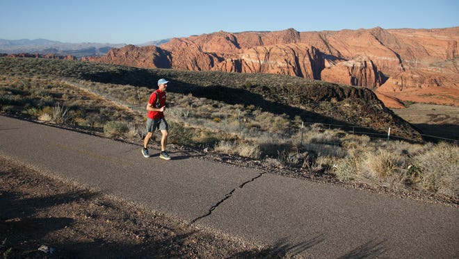 Cory Reese runs on the bike trail Friday beside state Route 18 overlooking Snow Canyon State Park as he makes his way towards the St. George Marathon starting line on the first of four times he'll run the 26.2 mile course. Reese plans on running the St. George Marathon with the rest of the field as the last leg of his 104.8 mile quadruple marathon run.