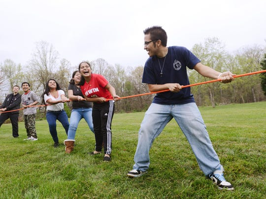 Melvis Madrigal, a mentor with M.A.N.O.S., looks back at his mentees as they play a game of tug-o-war during a meeting of the Latino outreach program at Emma Methodist Church. The program partners with Warren Wilson College and Children First / Communities in Schools to provide mentors to the students in the program and support their parents.
