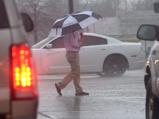 A man makes his way between cars on Kings Highway as the rain begins to fall Tuesday.