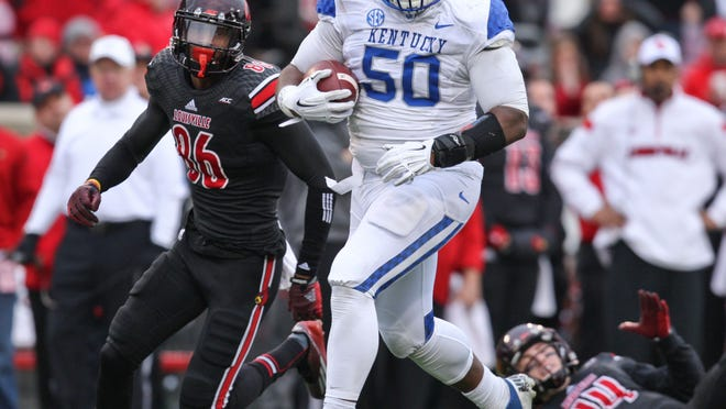 Kentucky defensive tackle Mike Douglas rumbles for a touchdown in the second half Saturday. It wasn't enough as UK fell to Louisville 44-40. Nov. 29, 2014 By Matt Stone/The C-J