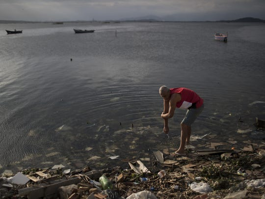 A man washes himself in the polluted waters of Guanabara Bay in Rio de Janeiro, Brazil, Saturday, July 30, 2016.
