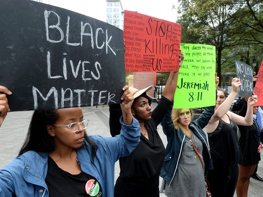 Queens University senior Hiwot Hailu, left and junior Jocelyn Purdie, second from left, were among the people gathered at Trade and Tryon Streets to protest a police officer's shooting Tuesday of Keith Lamont Scott, in uptown Charlotte, N.C., Wednesday afternoon, Sept. 21, 2016.  (Jeff Siner/The Charlotte Observer via AP)