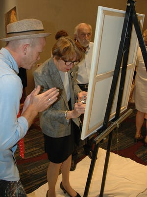 Painter Ryan McKain assists Linda White with adding her portrait to the Arts Awards artwork.