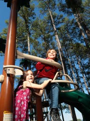 Scarlet Kean, left, and Sully Kean, both of Loganville, Georgia, play on new campground equipment at South Cove County Park in Seneca.