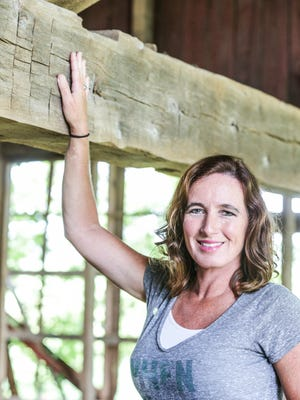 Angie Crouse, owner of Reclaimed Barns and Beams in Shelbyville Ind. showcases a uniquely large original barn beam handcrafted around the time of the Civil War, which harvested by the company, Wednesday, July 12, 2017. The company harvests wood from old barns for furniture and home accents and shares the history of the barn with its customers across the country.