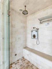 The master bathroom features tile stall shower with two shower heads.