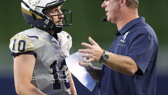 Hoban quarterback Shane Hamm speaks with coach Tim Tyrrell during a game against St. Vincent-St. Mary at InfoCision Stadium on Sept. 27, 2019, in Akron, Ohio.